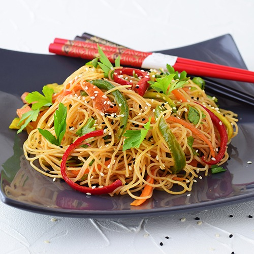 Black plate of cold noodle salad with red and black chopsticks