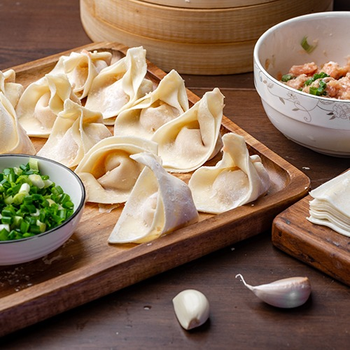 Wooden plate of folded wonton wrappers with bowl of pork meat and spring onions
